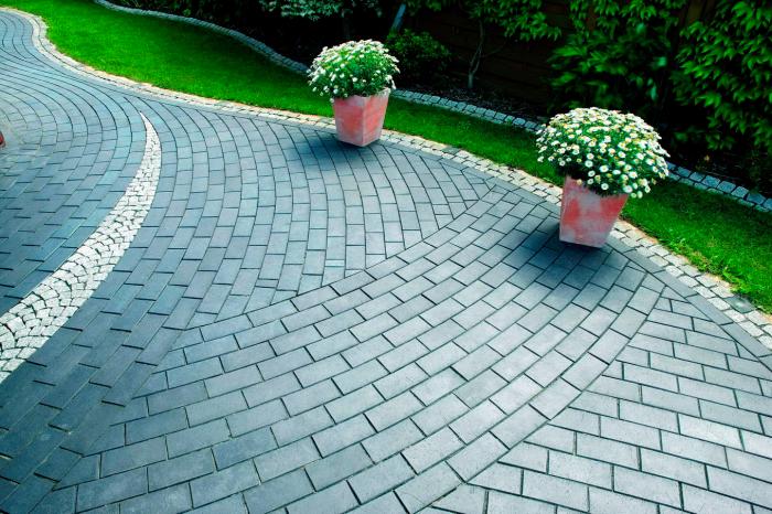 Классическая садовая дорожка, выложенная хорошо обработанным темным кирпичом.