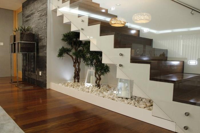 Пространство под лестницей целесообразно заполнить мелколистными экзотическими растениями.