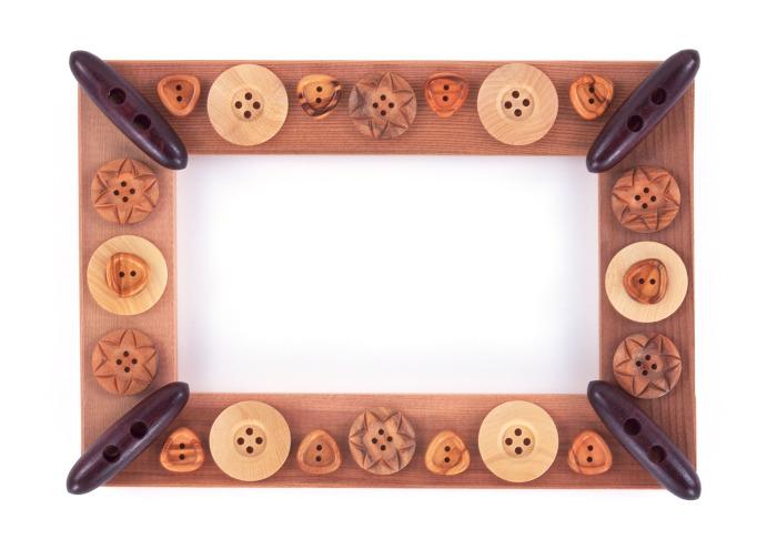 Рамка для картины украшенная пуговицами разной формы.