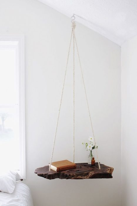 Оригинальная прикроватная подвесная тумбочка, изготовленная из цельного куска тёмной древесины.