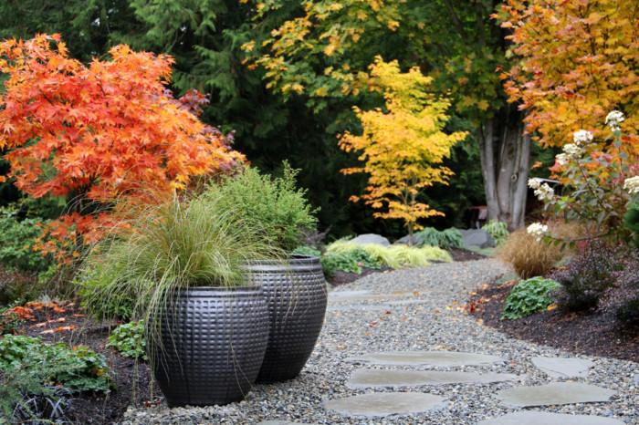 Прекрасный вариант оформить пространство садового участка при помощи темных кашпо.