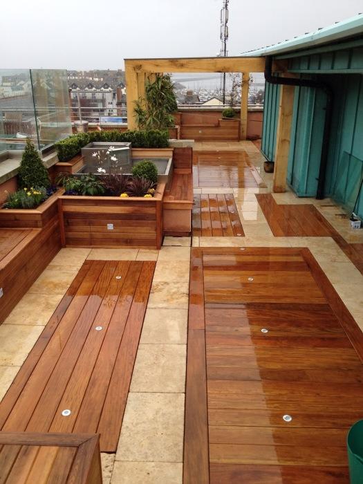 Деревянная скамейка, которая по стилю и цвету соответствует различным деревянным конструкциям на территории дачного участка.