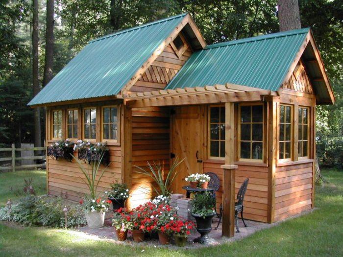 Удобная закрытая беседка на природе в виде маленького дома для дачного участка.