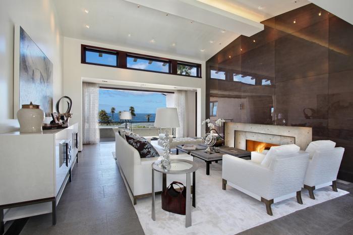 Гостиная комната, оформленная преимущественно в нейтральных тонах, с небольшим диваном светлого оттенка, невысоким журнальным столиком и акцентной стеной контрастного коричневого цвета.