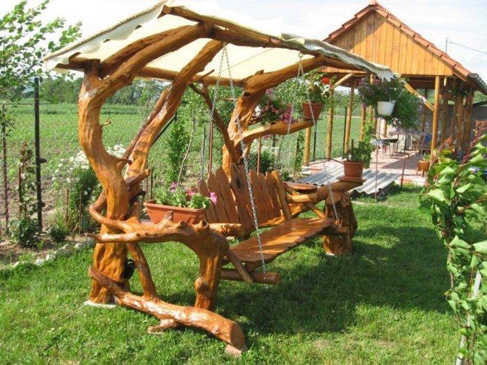 Деревянная качель создаст интересную и необычную обстановку в любом саду.