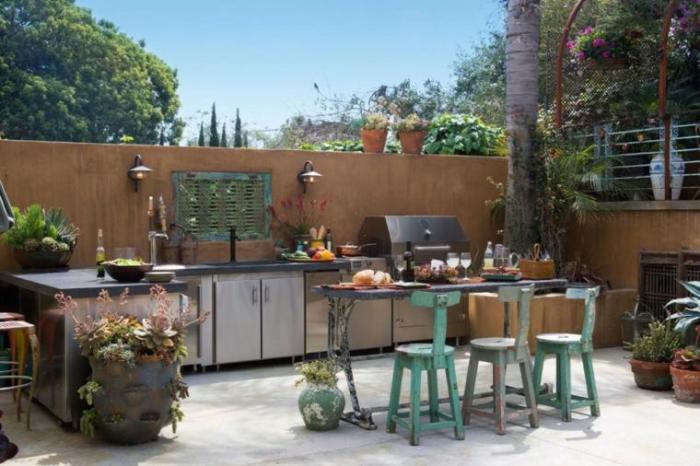 Оградите летнюю кухню от посторонних глаз высоким каменным забором.
