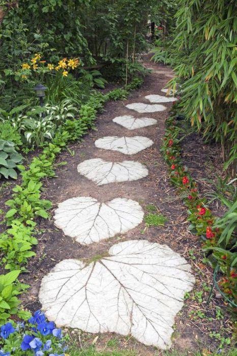 Садовая дорожка, сделанная из больших бетонных листьев на территории дачного участка.