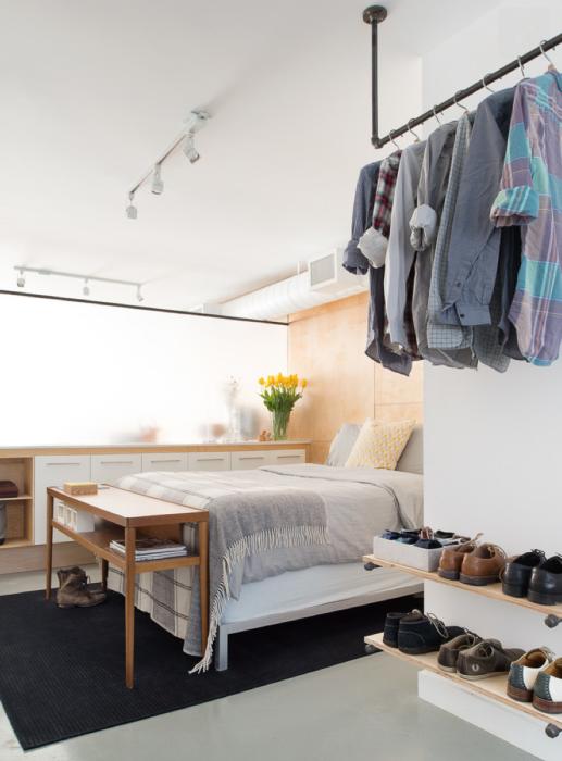 Обыкновенная металлическая труба и деревянные полочки позволят создать даже в небольшой спальной комнате гардероб.