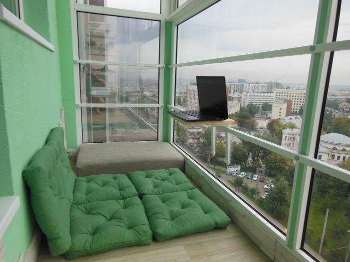 Лоджия в стиле минимализма с большими панельными окнами и уютным местом для вечерних посиделок.