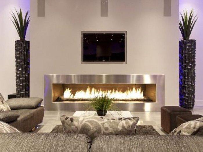 Камин, расположенный в зане для просмотра телевизора может стать одним из центральных звеньев современного интерьера.