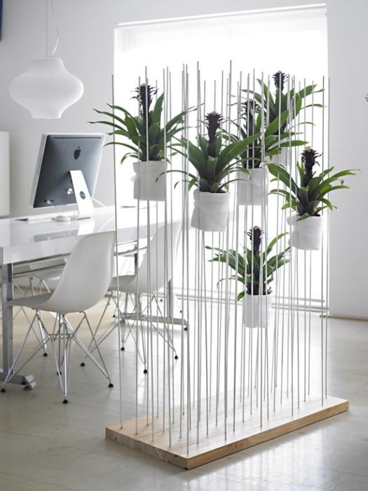 Рабочая зона компактно отделена от основного помещения перегородкой из металлических штырей, на которых насажены горшки с комнатными растениями.