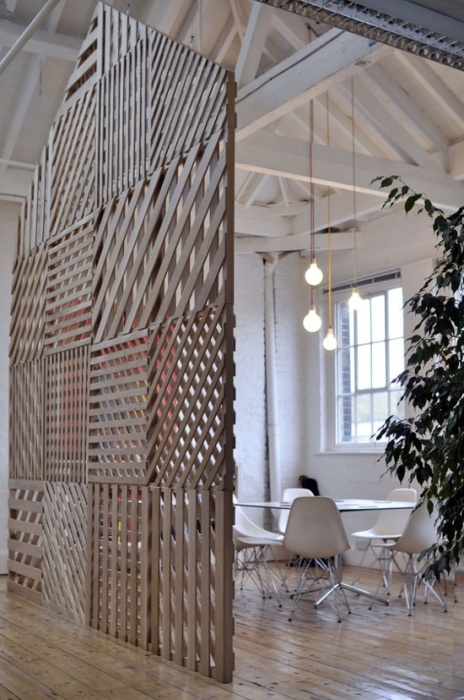 Высокая деревянная перегородка может использоваться в качестве зонирующего элемента в любом просторном помещении загородного дома.