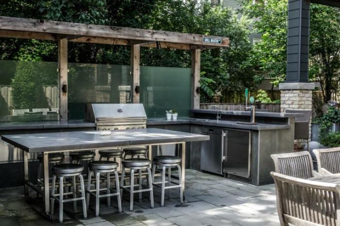Оригинальный дизайн-проект летней кухни с блеском нержавеющей стали и прохладой каменных покрытий.