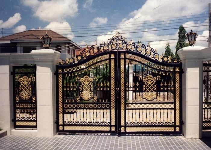 Металлические ворота с кованными элементами золотистого цвета.