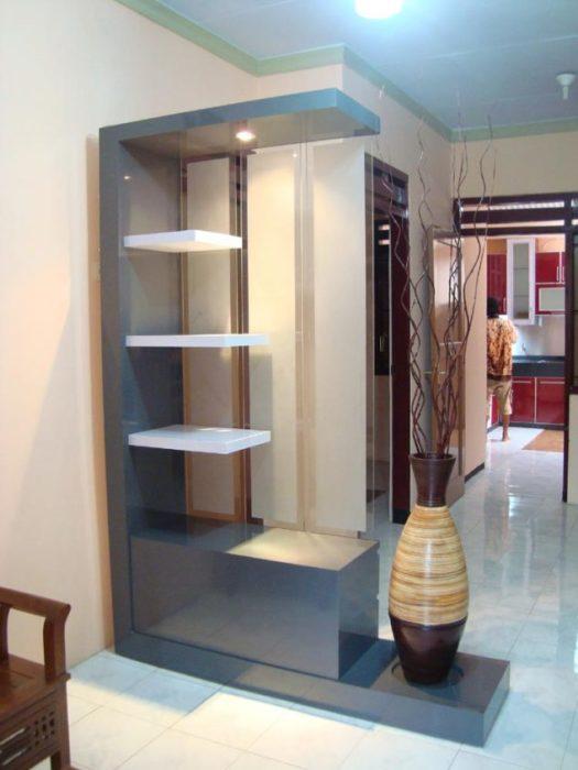 Современная гостиная комната в стиле минимализм, с небольшим стеллажом нейтрального серого оттенка, который максимально правильно разделяет пространство.