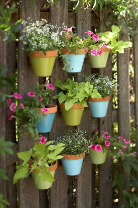 Деревянный забор с прикрепленными к нему цветочными горшками станет эффектным украшением современного садового участка.