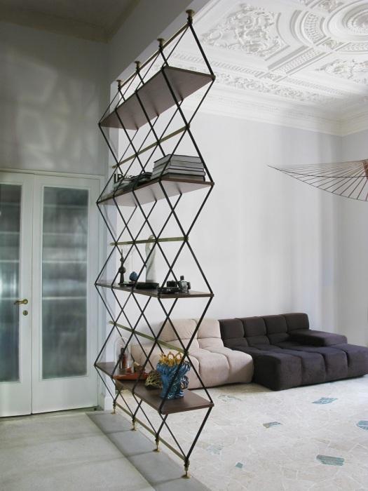 Стеллаж необычной конструкции с кованными креплениями, разделяющий гостиную комнату и прихожую.