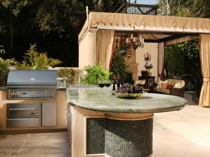 Летняя кухня со спрятанной под навесом мебелью сразу же привлечёт внимание гостей.