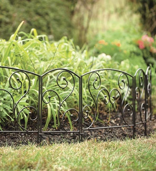 Аккуратно огороженная металлическим декоративным кованым забором клумба.