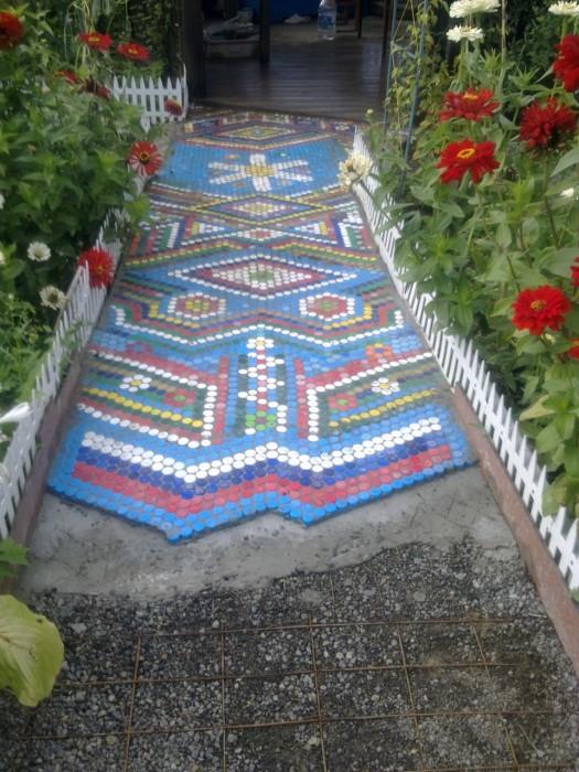 Садовая дорожка, выложенная в виде мозаики из пластмассовых крышечек.