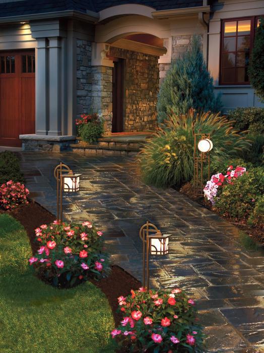 Правильно подобранное освещение и оригинальная цветовая гамма садовых дорожек на территории современного дачного участка.