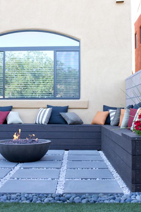 Для обустройства места возле огня достаточно смонтировать небольшую лавочку из деревянных досок и покрасить её в соответствии с цветовыми требованиями ландшафтного дизайна.