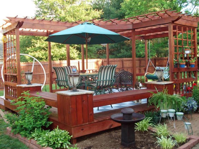 Роскошная деревянная площадка для отдыха на заднем дворе с качелями, навесным тентом и садовой мебелью.