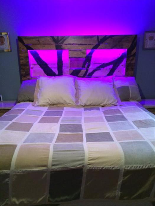 Бюджетная кровать из поддонов с неоновой подсветкой у изголовья.