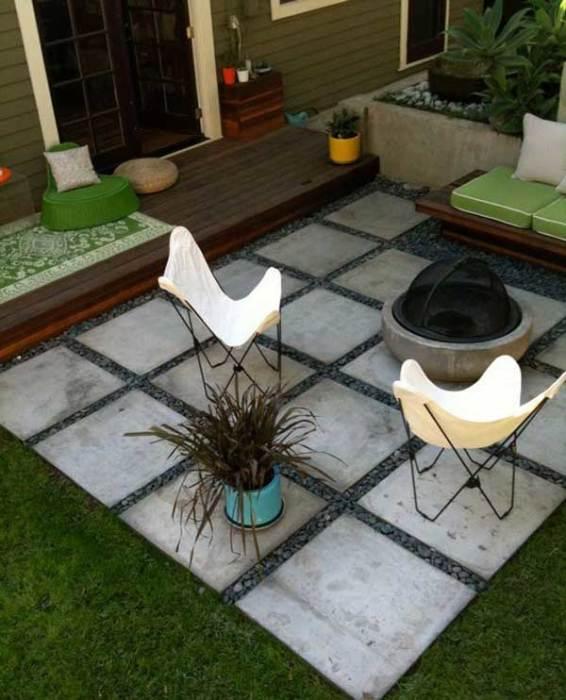 Простая площадка, вымощенная большими бетонными плитами, с небольшим комнатным кашпо, удобными стульчиками и бетонным очагом.