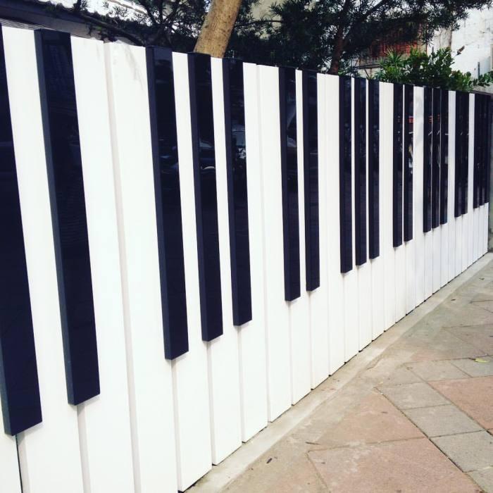 Металлический забор, который выглядит как струнный клавишный музыкальный инструмент с ударным способом звукоизвлечения.