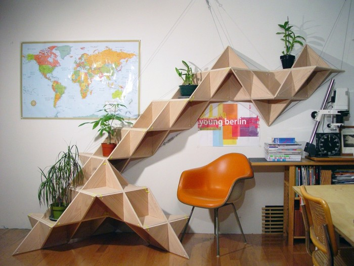 Трансформирующийся 3D стеллаж из светлой породы древесины.