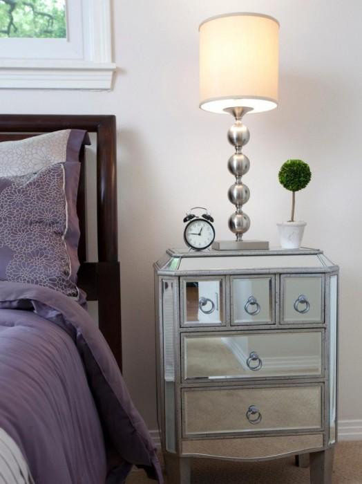 Металлическая прикроватная тумбочка, декорированная стеклом, станет завершающей деталью в современном интерьере спальни.
