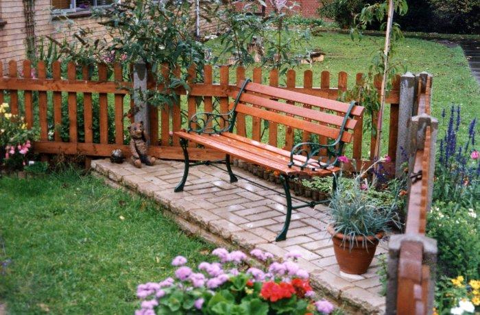 Стильная деревянная скамейка на небольшом садовом участке.