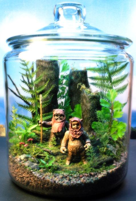 Террариум в стеклянной банке с двумя фантастическими фигурками.