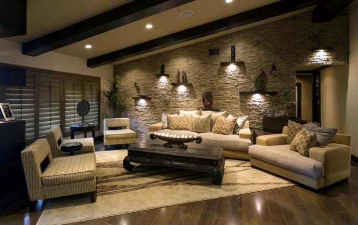 Стильный интерьер гостиной комнаты, который создан при помощи отделки одной стены искусственным камнем.