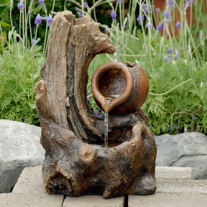 Удивительная композиция деревянной коряги и небольшого кувшина, объединенная в декоративный фонтан.