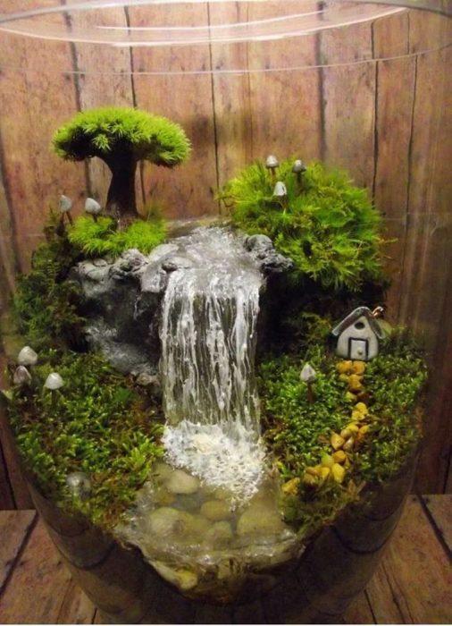 Мини-террариум в большом стеклянном сосуде с небольшим домиком и искусственным водопадом может стать прекрасным украшением для любого садового участка.