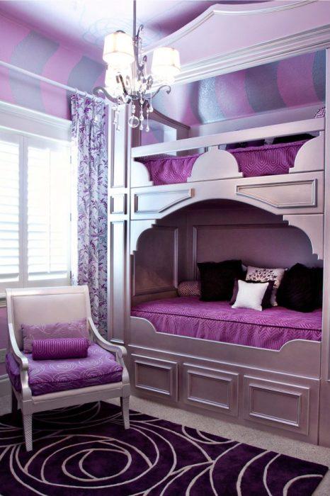 Двухъярусная кровать с подсветкой, отлично вписывающаяся в фиолетовый интерьер спальной комнаты.