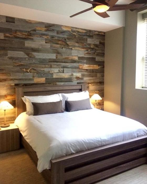 Стена у изголовья кровати, обшитая разными породами древесины.