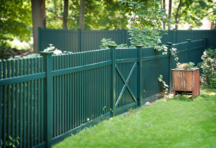 Классический штакетный забор зеленого цвета может стать красивым декоративным дополнением к ландшафтному дизайну.