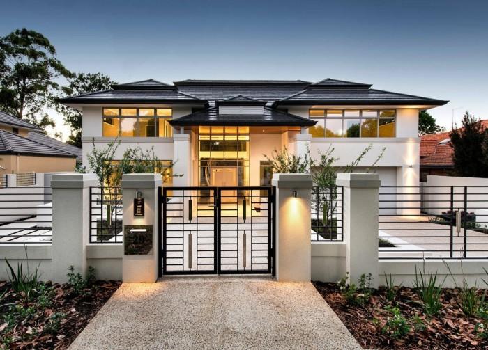 Роскошный кованый забор - прекрасное украшение фасада загородного дома.