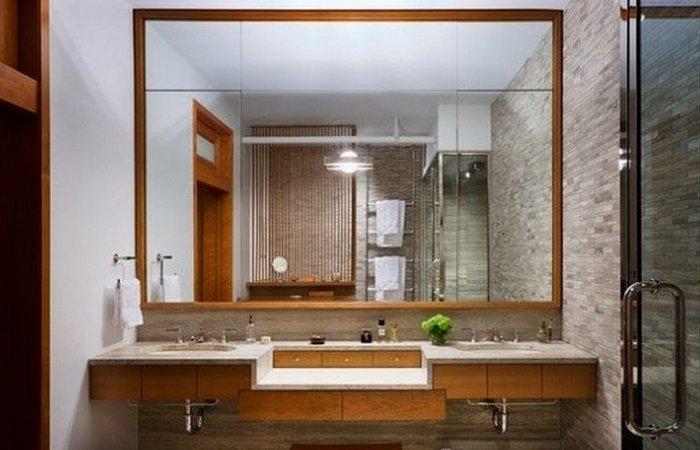 Большое зеркало с обрамлением в ванной комнате.