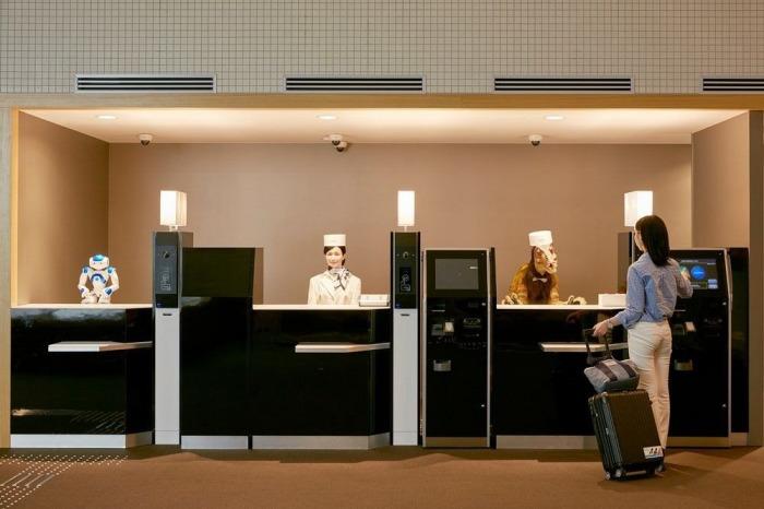 Три робота-гуманоида за столом регистрации гостей.