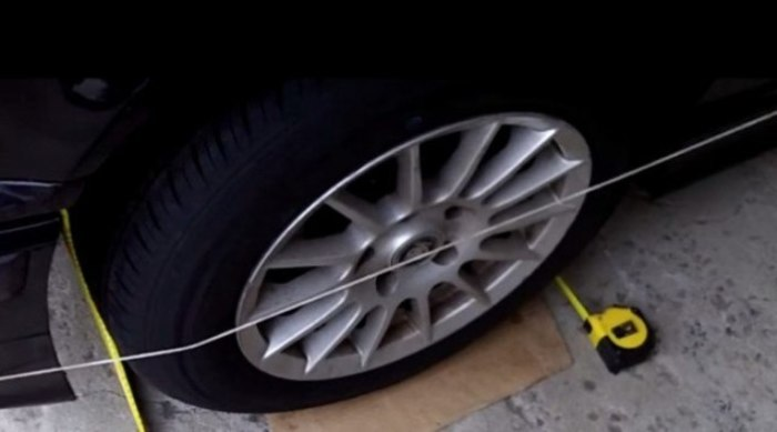Настраиваем развал по натянутой нитке. | Фото: youtube.com.