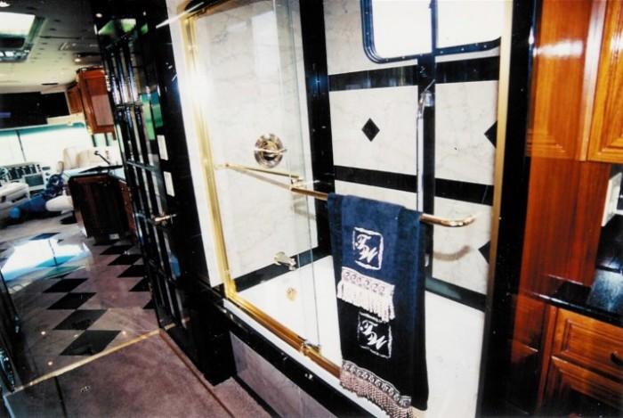 За стеклянной дверью с латунной отделкой находится душевая кабинка. | Фото: camillc.com.