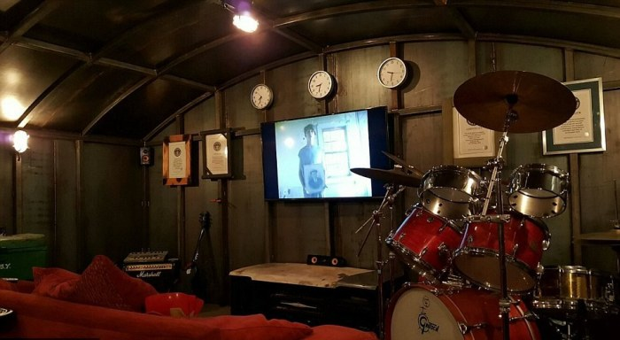 Любимая барабанная установка Колина и плазма на стене.