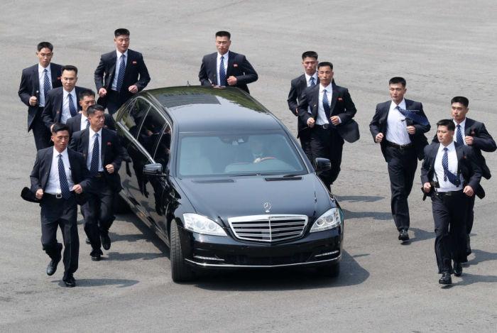 Северокорейские телохранители бегут рядом с автомобилем, перевозящим лидера КНДР Ким Чен Ына. | Фото: cheatsheet.com.