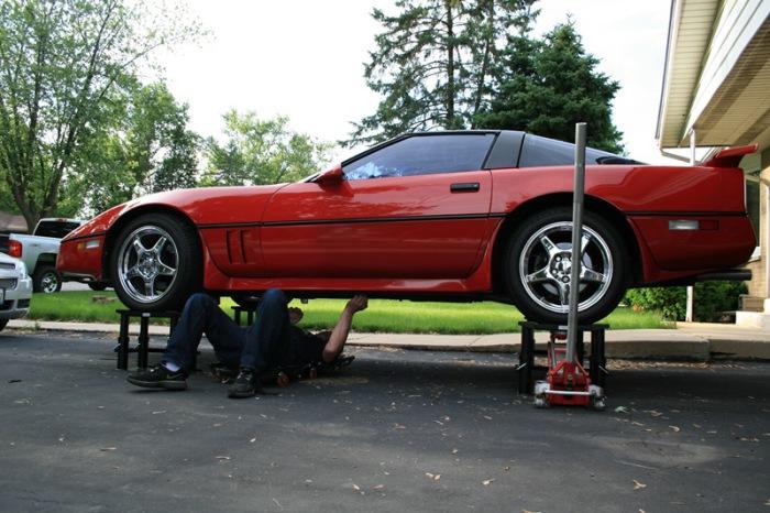 Слесарь ремонтирует Chevrolet Corvette, стоящий на стойках Lift Stand.