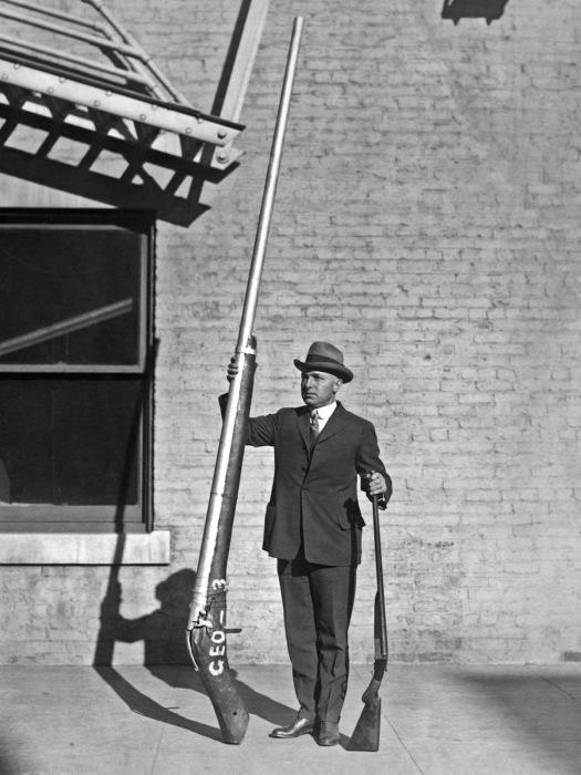 Глава егерской службы США демонстрирует изъятое гладкоствольное ружье длиной 3,25 метра весом 115 кг, которое использовалось для охоты на уток, 1920 год. | Фото: rarehistoricalphotos.com.