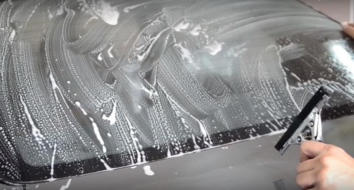 Обильно смачиваем стекло водой с шампунем или мылом. | Фото: youtube.com.